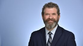 smiling man with beard, suit, tie